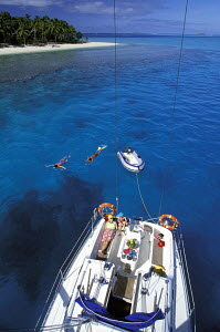 Aerial view of guests of a charter sailing yacht, moored near a palm-tree fringed island, relaxing onboard and snorkeling in the clear water during a cruise around the Vava'u Island Group, Tonga, Sout... - Neil Rabinowitz