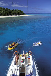 Aerial view of guests of a charter sailing yacht, moored near a palm-tree fringed island, relaxing onboard and playing in an inflatable dinghy during a cruise around the Vava'u Island Group, Tonga, So... - Neil Rabinowitz