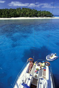 Aerial view of guests of a charter sailing yacht, moored near a palm-tree fringed island, relaxing onboard during a cruise around the Vava'u Island Group, Tonga, South Pacific. - Neil Rabinowitz
