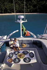 Couple dining on the aft deck of a charter catamaran during a cruise in the Caribbean. - Neil Rabinowitz