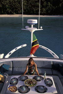Woman dining on the aft deck of a charter catamaran during a cruise in the Caribbean. - Neil Rabinowitz