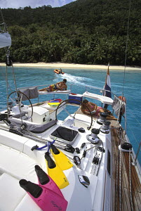 Guests relaxing onboard a charter sailing yacht moored near an island in the Virgin Islands, Caribbean. - Neil Rabinowitz
