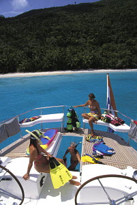 Guests onboard a charter sailing yacht moored near an island in the Virgin Islands, Caribbean. - Neil Rabinowitz