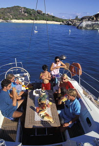 Guests dining on the aft deck of a charter sailing yacht moored in the Virgin Islands, Caribbean. - Neil Rabinowitz