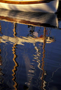 Reflection of a wooden boat on calm water. - Neil Rabinowitz