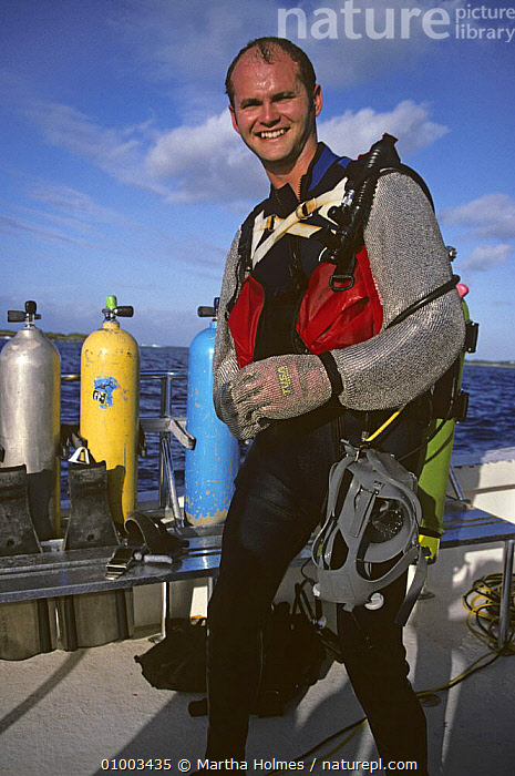 """Simon King on location, wearing chain mail shark suit for television series """"Hotshots"""", June 1994  ,  DIVING,NHU,PEOPLE,PORTRAITS,VERTICAL  ,  Martha Holmes"""