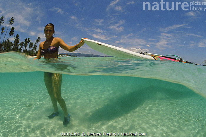 Windsurfer in sea bringing surfboard ashore. Philippines  ,  HOLIDAYS,INTERESTING,LEISURE,PEOPLE,SOUTH EAST ASIA,SPLIT LEVEL,TOURISM,WATER PURSUITS,WOMAN,Asia,Concepts,SPORTS, WATERSPORTS,Weather  ,  Jurgen Freund