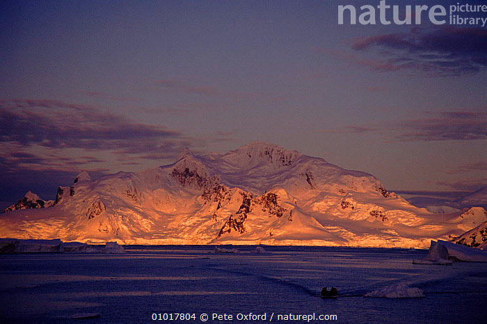 Antarctic Penninsula and tourists in Zodiac boat. Antarctica  ,  PEOPLE,HORIZONTAL,SCENERY,ANTARCTIC,BOAT,ICE,ATMOSPHERIC,LEISURE,HOLIDAYS,SNOW,TOURISTS,TOURISM,PENNINSULA,MOUNTAINS,CONCEPTS  ,  Pete Oxford
