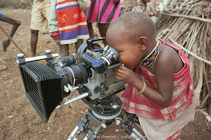 Masai child looking through the camera during filming OF BBC series Lifesense Masai Mara, Kenya, East Africa 1990  ,  AFRICA,CHILDREN,CULTURES,CUTE,MAASAI,NHU,PEOPLE,TRADITIONAL,TRIBES  ,  John Downer