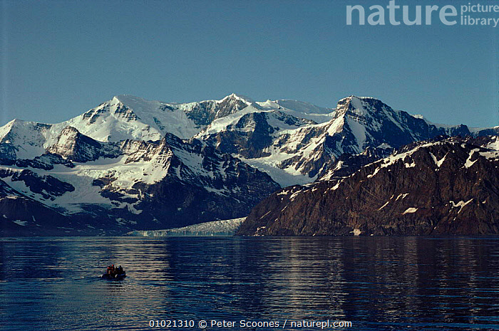 Inflatable boat approaches antarctic mountains and glacier. Antarctica, BOAT,GEOLOGY,GLACIERS,HORIZONTAL,INFLATABLE,MOUNTAINS,PEOPLE,RESEARCH,ROCK FORMATIONS,SNOW, PETER SCOONES
