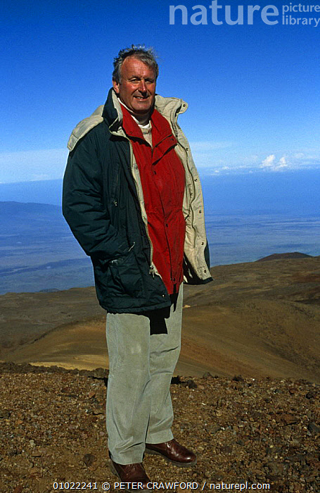Presenter Julian Pettifer on Mauna Kea, presenting BBC programme 'Global Sunrise', 1996, HAWAII,LANDSCAPES,NHU,PEOPLE,PORTRAITS,SUNRISE,USA,VERTICAL,VOLCANOES,North America,Geology, PETER CRAWFORD