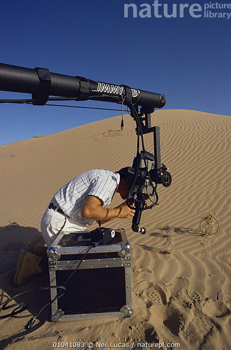 """Cameraman Gavin Thurston on location in the Sonoran Desert, California, using a Jimmy Jib to film plants for BBC television series """"Private Life of Plants"""", early 1990s  ,  CAMERA,CAMERAS,DESERTS,EQUIPMENT,FILMING,FILMING IN WILD,NHU,PEOPLE,SAND DUNES,TECHNIQUES,USA,VERTICAL,North America  ,  Neil Lucas"""
