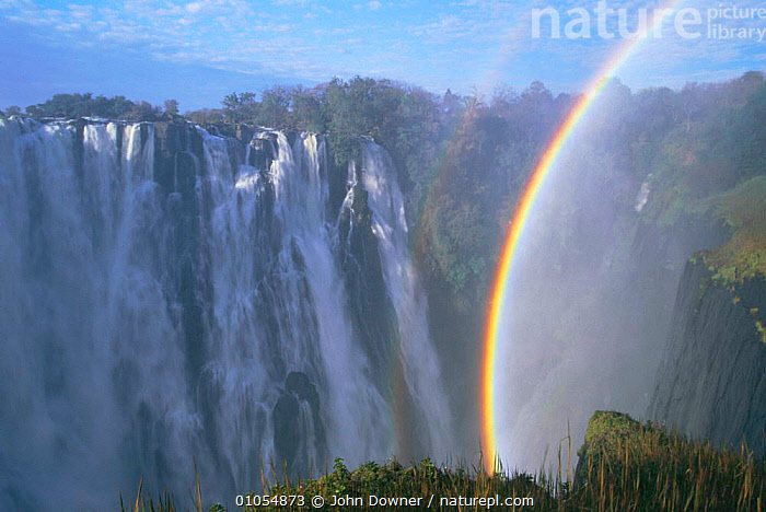 Victoria Falls showing rainbow. Zimbabwe, Southern Africa. Horizontal, rainbows  ,  RAINBOW,RIVERS,SOUTHERN AFRICA,WATERFALLS,LANDSCAPES,ATMOSPHERIC  ,  John Downer