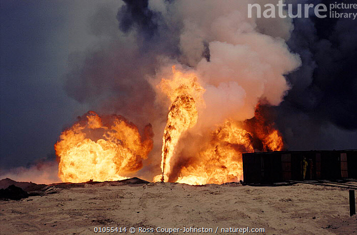 Burning oil well with water control from heat-shielding shed (post Guld war). Kuwait, Arabia  ,  BURNING,CRUDE OIL,DRAMATIC,FIRE,GULF,HORIZONTAL,OIL,PEOPLE,POLLUTION,POST,WAR,WELL,ARABIA  ,  Ross Couper-Johnston