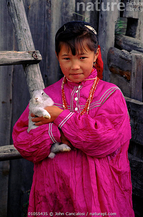 Mansi child in traditional dress holding rabbit, Siberia, Russia  ,  DRESS,MANSI,TRADITIONAL,PEOPLE,CANCALOSI,COLOURFUL,VERTICAL,,MAMMALS,PETS,CHILD,PINK,JCA,RABBIT,CIS  ,  John Cancalosi