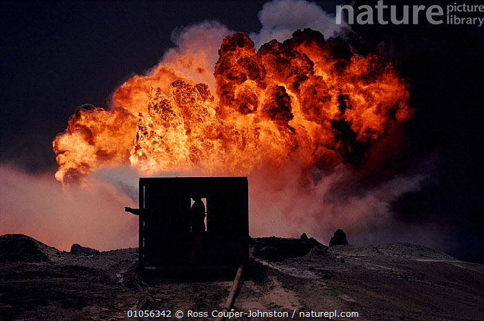 Spraying water on burning oil well from heat-shielding shed, Kuwait, post Gulf War.  ,  BURNING,CONTROL,COUPER JOHNSTON,CRUDE OIL,DRAMATIC,FIRE,GULF,OIL,PEOPLE,RCJ,VERTICAL,WATER,WELL,ARABIA  ,  Ross Couper-Johnston