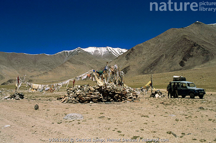 Land Rover and people next to prayer flags and 'ovoo' rock piles, Ladakh, North East India, ASIA,CULTURES,HIGHLANDS,INDIAN SUBCONTINENT,MOUNTAINS,PEOPLE,religious,spiritual,VEHICLES , LANDSCAPES,INDIAN-SUBCONTINENT, Gertrud & Helmut Denzau