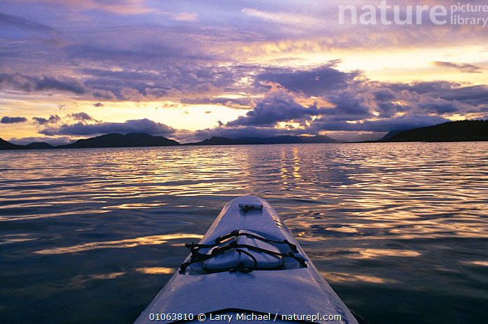Kayaking off coast of Alaska, USA, BOATS,COASTAL WATERS,COASTS,DUSK,KAYAKING,LEISURE,NORTH AMERICA,OUTDOOR PURSUITS,SKY,SUNSET,SURFACE,USA,WATER,WATER PURSUITS,SPORTS, WATERSPORTS, WATERSPORTS, WATERSPORTS, WATERSPORTS, Larry Michael