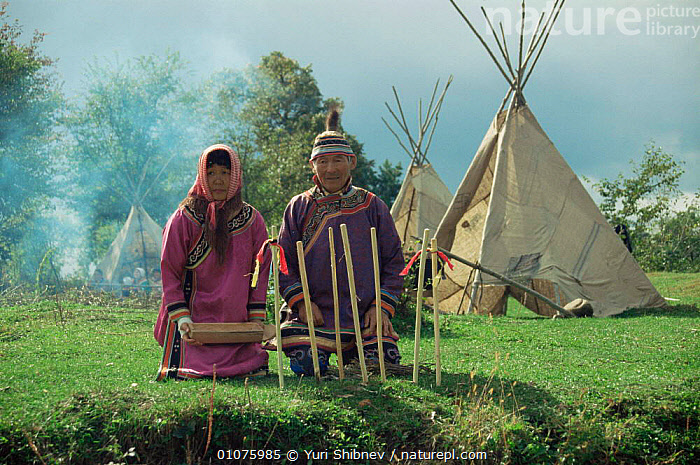 Udege couple in traditional clothing sitting outside traditional tent, Sikhote Alin, Primorsky region, Russia  (Ussuriland).  ,  ASIA,BUILDINGS,clothing,CULTURES,HOMES,MALE FEMALE PAIR,PEOPLE,primorskiy,RUSSIA,tents,TRADITIONAL,tribal,TRIBES,CIS  ,  Yuri Shibnev
