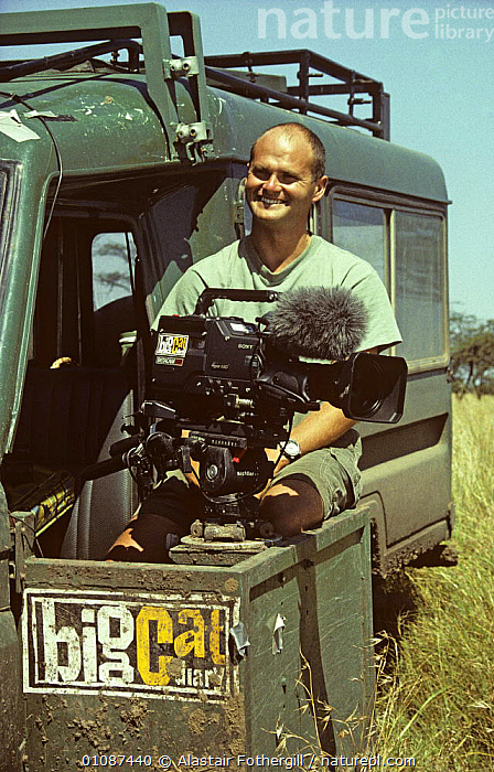 """Simon King on location filming for BBC series """"Big Cat Diary"""". Kenya, 1996  ,  AFRICA,CAMERA,CAMERAS,EAST AFRICA,FILMING,FILMING IN WILD,NHU,PEOPLE,PORTRAITS,SAVANNA,VEHICLES,VERTICAL,Grassland  ,  Alastair Fothergill"""