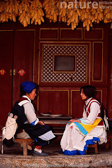 Naxi woman wearing traditional cape with 7 stars on back, Suhe village, Lijiang, Yunnan, China. Ethnic minority group. 2002  ,  ASIA,BUILDINGS,CHINESE,CORN,COSTUME,ETHNIC,GROUP,MAIZE,PEOPLE,PO,TRADITIONAL,TRIBES,TWO,VERTICAL,VILLAGE,WOMEN,CHINA  ,  Pete Oxford