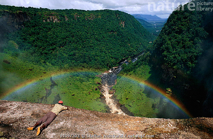 Man overlooking Kaieteur Falls Gorge with rainbow, Guyana, South America., AMERICA,GORGES,LANDSCAPES,PEOPLE,RAINFOREST,RIVERS,SCENICS,SPRAY,TROPICAL,TROPICAL RAINFOREST,SOUTH-AMERICA, Staffan Widstrand