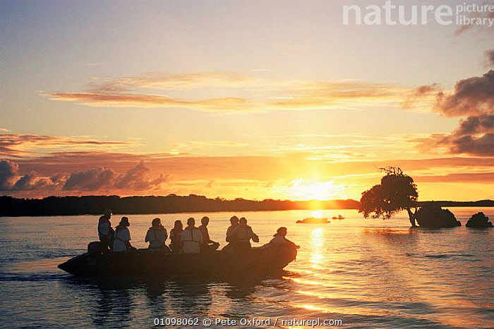 Tourists in zodiac boat at sunset, Central lagoon, Aldabra Island, Seychelles, Indian Ocean, BOATS,COASTAL WATERS,COASTS,DUSK,EVENING,HOLIDAYS,INDIAN OCEAN,ISLANDS,MARINE,PEOPLE,SEA,SEYCHELLES,SILHOUETTES,SUN,SUNLIGHT,SUNSET,TOURISM,TROPICAL,WATER,Concepts,INDIAN OCEAN ISLANDS, Pete Oxford