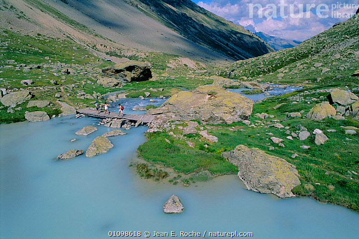 Blue waters of river flowing off the Alps + hikers  Ecrins, France  ,  ALPS,COLD,ECRINS,HIKING,HORIZONTAL,LANDSCAPES,LEISURE,MOUNTAINS,PEOPLE,RIVERS,WALKING,Europe  ,  Jean E. Roche