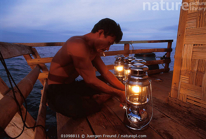 Rakit custodian at Funae fishery raft lights lanterns to attract fish to surface at night for fishermen to catch at dawn. Boats pay to fish in a Rakit area. Custodian spends years living at sea. 2000  ,  ASIA,FISHERIES,FISHERY,FISHING,HORIZONTAL,JFR,LANTERNS,LIGHT,MAN,NIGHT,PEOPLE,SEA,SOUTH EAST ASIA,SULAWESI,SULU,SULU SULAWESI,TRADITIONAL,SOUTH-EAST-ASIA,INDONESIA  ,  Jurgen Freund