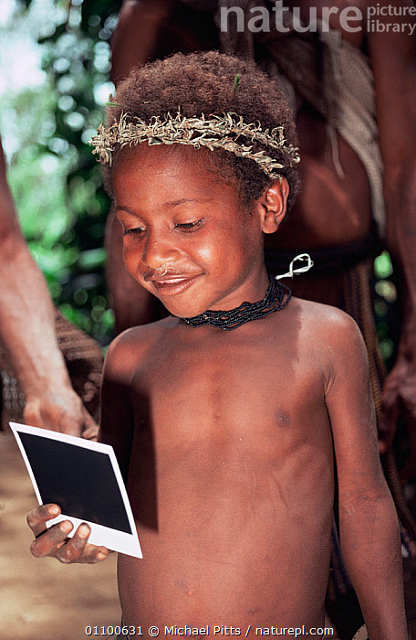 Young Huli boy looking at polaroid photo of himself, Central Highlands, Papua New Guinea  ,  ASIA,CHILD,CHILDREN,CULTURES,HIGHLANDS,JUVENILE,MALES,MODERN,PAPUA NEW GUINEA,PORTRAITS,SOUTH EAST ASIA,TRADITIONAL,TRIBES,VERTICAL,WEST-AFRICA  ,  Michael Pitts