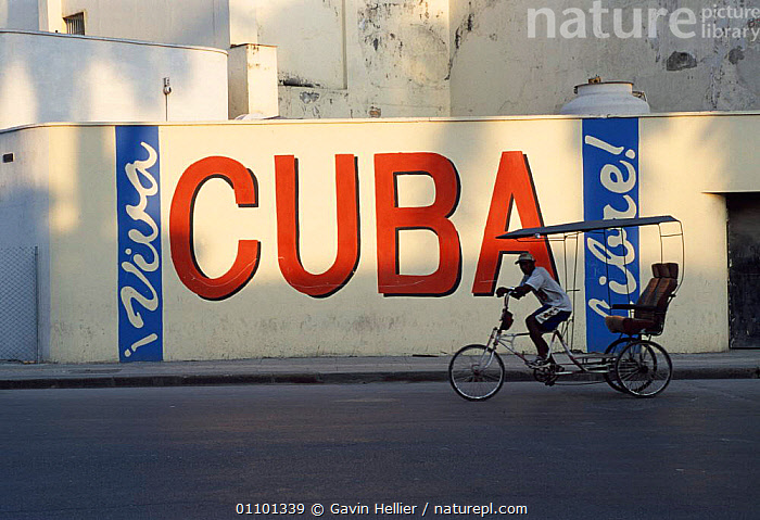 Man on rickshaw cycling past Cuba sign, Old-Havana, Havana, Cuba Caribbean  ,  BICYCLE,BILLBOARD,BOARDS,BUILDINGS,CARIBBEAN,CYCLING,GHE,HAVANA,HORIZONTAL,LOCAL,MAN,PEOPLE,RICKSHAW,SIGN,SIGNS,TOWN,TOWNS,TRANSPORT,TRAVEL,TRAVELLING,West Indies,SPORTS  ,  Gavin Hellier