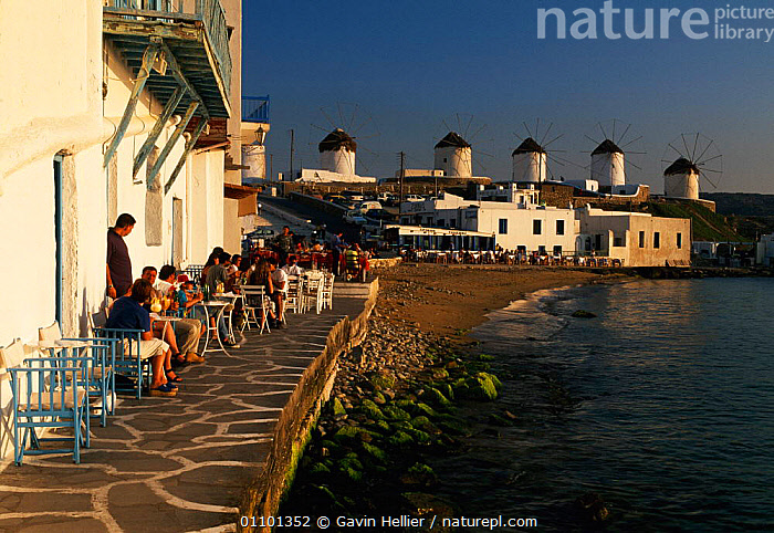 Restaurants in 'Little Venice', Hora, Mykonos, Cyclades windmills in background Greece Europe  ,  BUILDINGS,CAFE,COASTS,CONCEPTS,CYCLADES,EATING,EVENING,GHE,GREEK,HOLIDAYS,HORIZONTAL,ISLANDS,LANDSCAPES,MEDITERRANEAN,MYKONOS,PEOPLE,RESORT,RESTAURANTS,SEA,SEAFRONT,TABLES,TOURISM,TOURIST,TOURISTS,TRAVEL,WINDMILLS,Europe  ,  Gavin Hellier