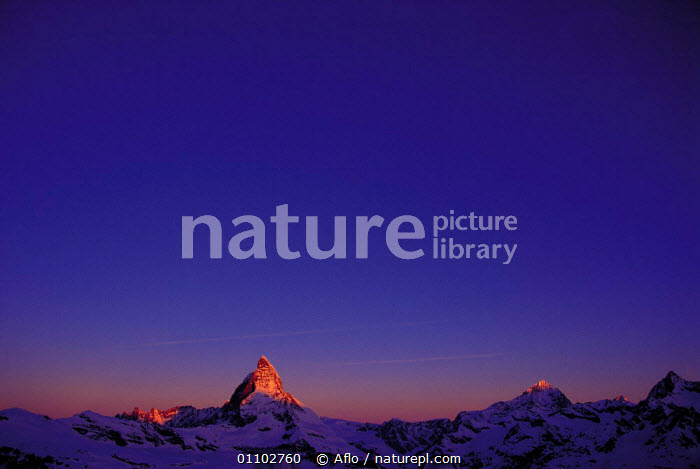 N-22006 The Alps at dawn with the Matterhorn peak, Zermatt, Switzerland. FOR SALE IN THE UNITED KINGDOM ONLY, AFLO,ALPINE,ALPS,CALM,DAWN,DRAMATIC,EARLY,HORIZONTAL,LANDMARK,MORNING,MOUNTAIN,MOUNTAINS,N 22006,NATURE CATALOGUE,PEAKS,POINT,POINTED,PURPLE,RISING,SKY,SNOW,SUN,SUNLIGHT,SUNRISE,TRAVEL,ZERMATT,EUROPE, Aflo