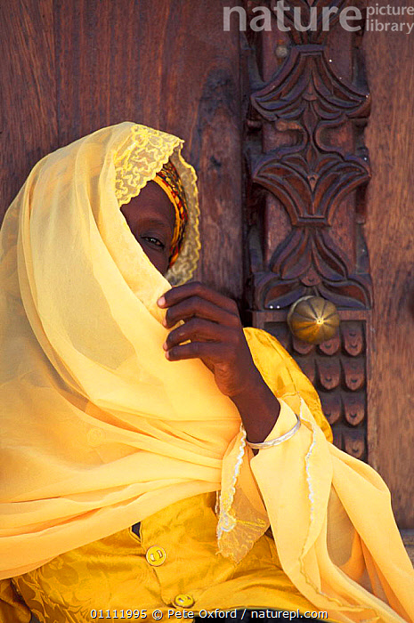 Local muslim woman beside carved studded door. Stone Town, Zanzibar, Tanzania  ,  AFRICA,CLOTHES,DOOR,PEOPLE,TRADITIONAL,YELLOW,EAST-AFRICA  ,  Pete Oxford
