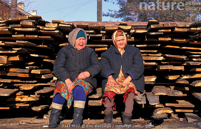 Two women sitting beside pile of timber, Lake Baikal, Siberia, Russia  ,  FORESTRY,PEOPLE,WOOD,WOODEN ,RUSSIA,CIS  ,  Eric Baccega