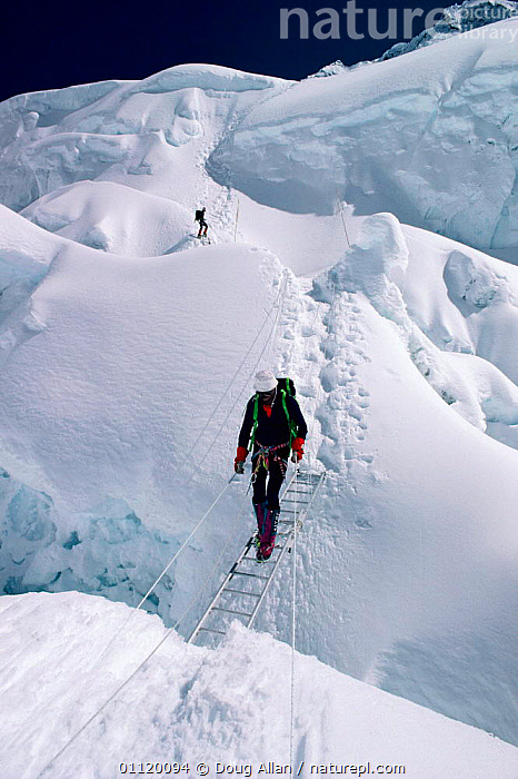 Climber crossing a crevasse, Khumbu Ice Fall, Mt Everest, Nepal.  ,  ASIA,ADVENTURE,DANGEROUS,CLIMBING,PEOPLE,MOUNTAINS,LADDER,LANDSCAPES,SNOW,VERTICAL,INDIAN-SUBCONTINENT  ,  Doug Allan