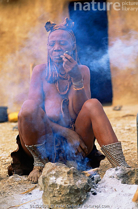 Married Himba woman smoking pipe with Erembe headdress, Kaokoland, Namibia 1999.  ,  AFRICA,CULTURES,PEOPLE,SMOKE,SOUTHERN AFRICA,TRADITIONAL,TRIBES,VERTICAL,WOMAN  ,  Pete Oxford