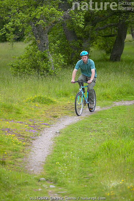 Nature Picture Library - Man cycling along woodland trail
