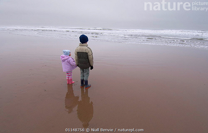 Children on a wet beach looking out to sea, Scotland, UK.  ,  BEACHES,COASTS,EUROPE,LANDSCAPES,PEOPLE,SEA,SEASIDE,UK,WATER,WINTER,United Kingdom,British, United Kingdom, United Kingdom  ,  Niall Benvie