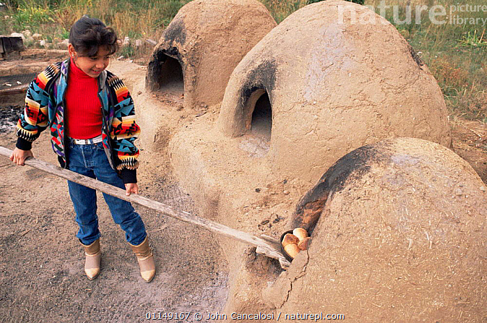 Native American child baking bread in clay oven, Taos Pueblo, New Mexico, USA  ,  CHILDREN,cooking,CULTURES,food,north america,ovens,PEOPLE,TRADITIONAL,USA,CENTRAL-AMERICA  ,  John Cancalosi