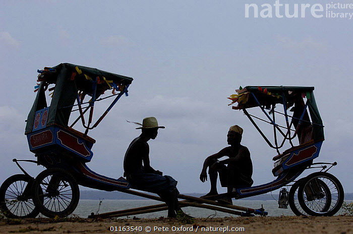 Local rickshaws (Pousse-pousses) introduced to Madagascar by the British missionaries. Majunga Town. NW MADAGASCAR  2005  ,  MADAGASCAR,PEOPLE,Pousse pousse,Rickshaw,SILHOUETTES,Transport,two  ,  Pete Oxford