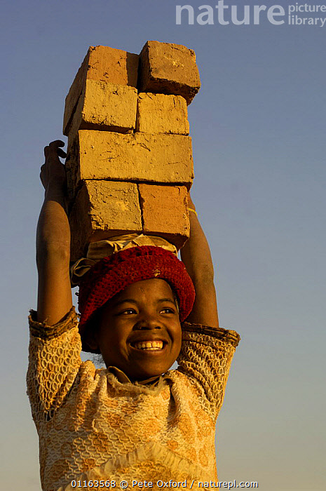 Child carrying bricks made by digging up surrounding soil, individually moulding the bricks, building kilns and using large quantities of fire wood. Madagascar  ,  AFRICA,TRADITIONAL,VERTICAL,WORKING,MADAGASCAR  ,  Pete Oxford