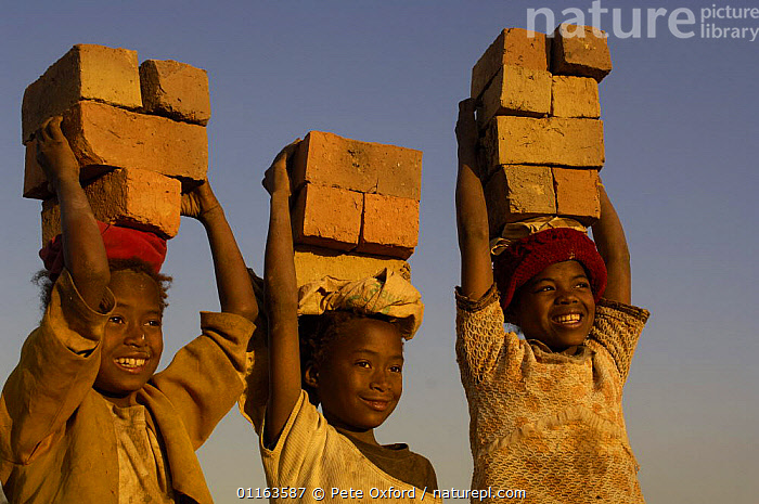 Children carrying bricks made by digging up surrounding soil, individually moulding the bricks, building kilns and using large quantities of fire wood. Madagascar  ,  MADAGASCAR,THREE,TRADITIONAL,WORKING  ,  Pete Oxford