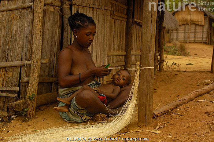 Sakalava woman working with Raffia from the Raffia palm (Raffia rarinifera) Ankarafantsika Nature Reserve, Western deciduous forest. MADAGASCAR 2005  ,  BABIES,crafts,MADAGASCAR,mother baby,PEOPLE,TRADITIONAL,TRIBES,weaving  ,  Pete Oxford