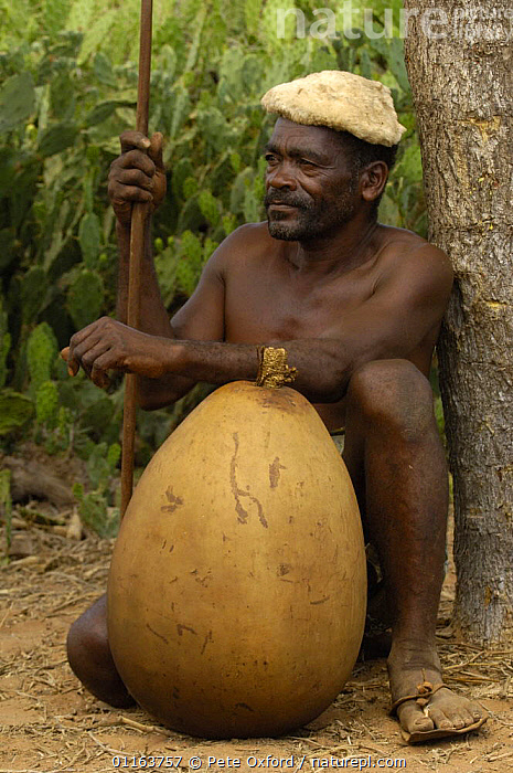 Antandroy herdsman wearing hat made from goat skin and shoes from Zebu skin. The gourd is for storing water or milk and the top is closed off with a corn cob. Spiny forest of Southern MADAGASCAR.  2005  ,  MADAGASCAR,PEOPLE,PORTRAITS,TRADITIONAL,TRIBES,VERTICAL  ,  Pete Oxford
