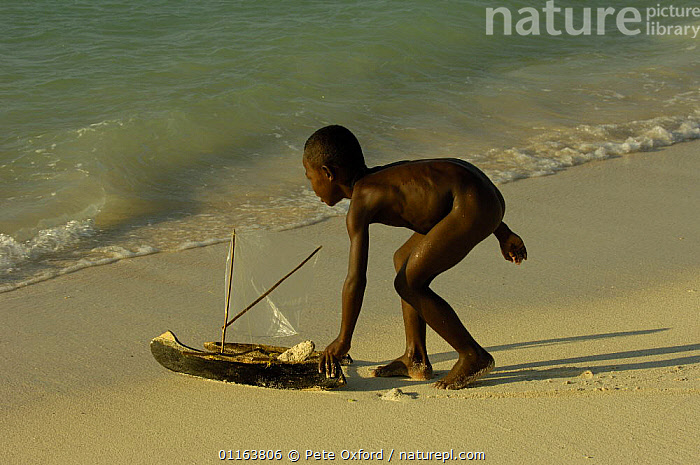 Vezo child playing on the beach with model pirogue. Beheloka Vezo fishing village. South-western MADAGASCAR 2005  ,  BOATS,CHILDREN,COASTS,MADAGASCAR,PEOPLE,play,TRADITIONAL,Communication  ,  Pete Oxford