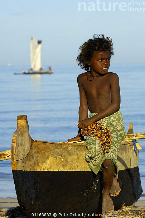 Child selling necklaces on the beach made from seeds and shells found locally. Mangily, near Ifaty. South-western MADAGASCAR  ,  CHILD,CHILDREN,COASTS,MADAGASCAR,SEEDS,shells,TRADE,TRADITIONAL,VERTICAL  ,  Pete Oxford