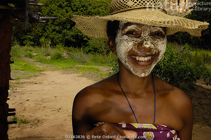Local woman with sandalwood face mask - used as sun protection and a beautification. Isalo National Park, MADAGASCAR   2005  ,  FACES,hats,MADAGASCAR,PEOPLE,PORTRAITS,TRADITIONAL  ,  Pete Oxford