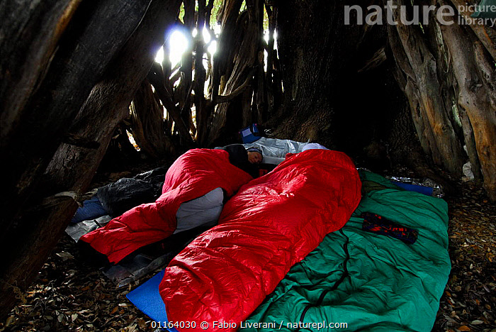 People in sleeping bags resting during day, in traditional sardinian goat hut, Sardinia, Italy  ,  EUROPE,PEOPLE,RESTING,SLEEPING , Supramonte NP, national park  ,  Fabio Liverani
