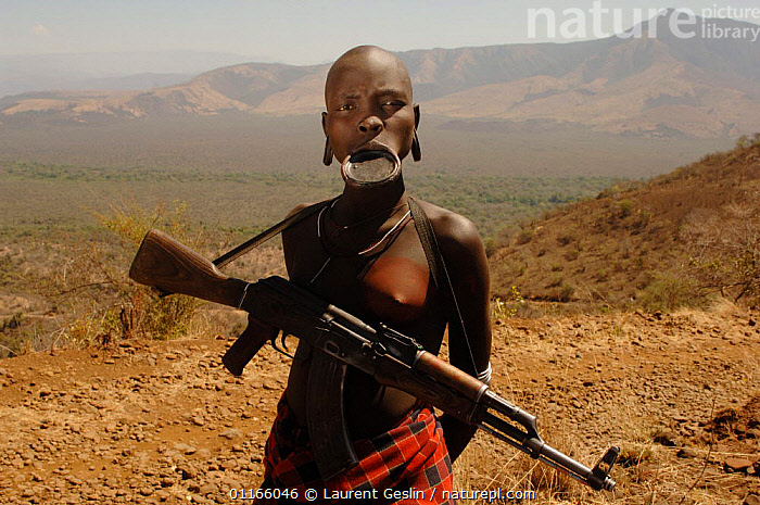 Young Mursi woman with clay plate in lower lip, holding her Kalashnikov rifle (result of the cold war in Africa), Omo valley, Ethiopia, 2006  ,  EAST AFRICA,GUNS,LANDSCAPES,PEOPLE,PORTRAITS,TRADITIONAL,TRIBES,WOMEN,Africa,EAST-AFRICA,Catalogue1F  ,  Laurent Geslin